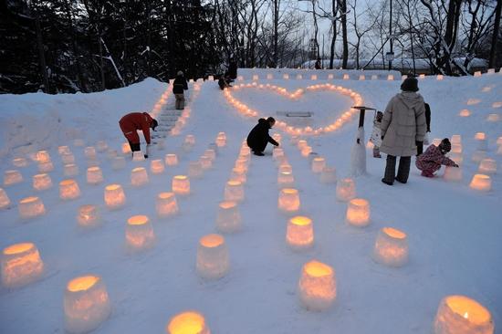 Orang-orang menyalakan api saat Jozankei Yuki Toro Festival