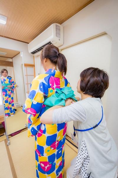 Petugas membantu mengenakan kimono